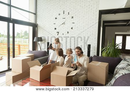 Young happy family with kids unpacking boxes together sitting on sofa in modern living room of country house moving settling in new home, children helping parents to pack stuff move out relocating