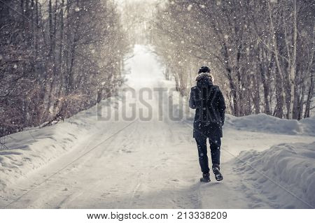 Lonely woman walking on snowy winter road among trees  alley with light at the end of the way in cold winter  day during snowfall  with copy space