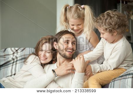 Cheerful parents and little children laughing having fun at home, wife with kids embracing hugging husband showing dad love, care and support, cozy loving family of four together, happy fathers day