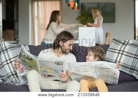 Happy dad and son reading newspapers together on couch, father with little boy looking at each other holding paper news, funny kid copying imitating daddy sitting at home on sofa, intelligent child