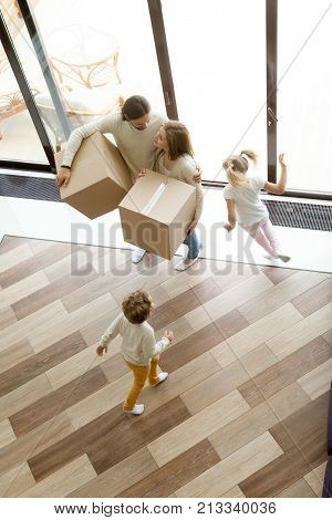 Family and children moving into new home, kids playing running around parents holding boxes standing in house hall together, happy couple with two children having fun move in, vertical top view