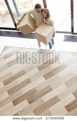 Happy couple coming into modern house through glass door holding boxes, smiling loving man and woman moving in new home with belongings, buying real estate, mortgage loan and relocation, top view