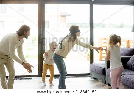 Blindfolded mother playing hide and seek game with father and kids hiding clapping hands at home, happy family having fun together on leisure in living room, parents children activities on weekend