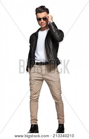 cool fashion man taking off his sunglasses on white background