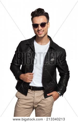 happy fashion man in sunglasses and leather jacket psing on white background