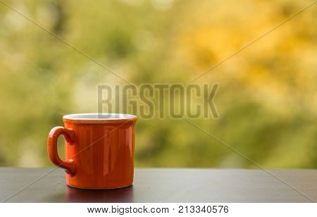 Red cup of hot steaming drink pot on a cafe wooden table outdoors