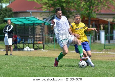 KAPOSVAR, HUNGARY - JUNE 11: Konrad Kiss (in white) in action at the Hungarian National Championship under 17 game between Kaposvari Rakoczi FC and Bajai LSE on June 11, 2011 in Kaposvar, Hungary.
