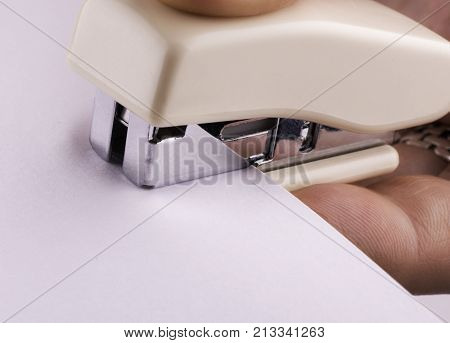 stapler for binding sheets of paper closeup.