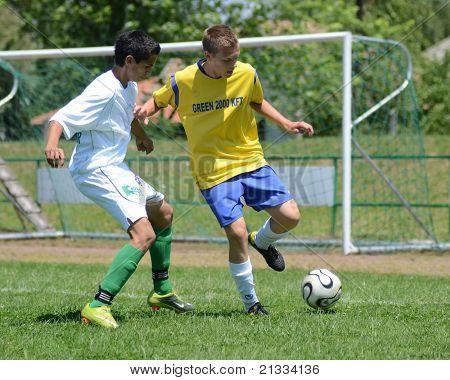 KAPOSVAR, HUNGARY - JUNE 11: Bence Vadasz (in white) in action at the Hungarian National Championship under 17 game between Kaposvari Rakoczi FC and Bajai LSE on June 11, 2011 in Kaposvar, Hungary.