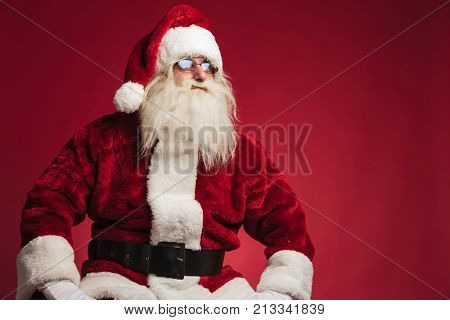 santa claus resting on a chair and looks to side on red background