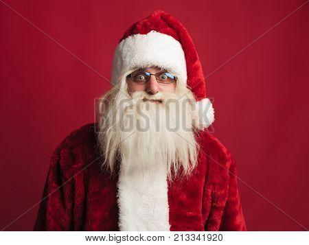 amazed santa claus on red studio background
