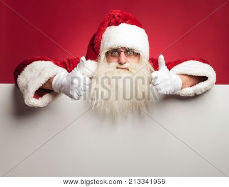 santa claus making the ok sign on top of a blank board on red background