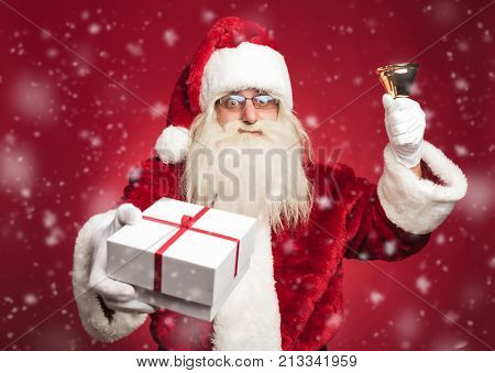 happy santa claus ringing his bell and offering a present to everybody while snowing on red background