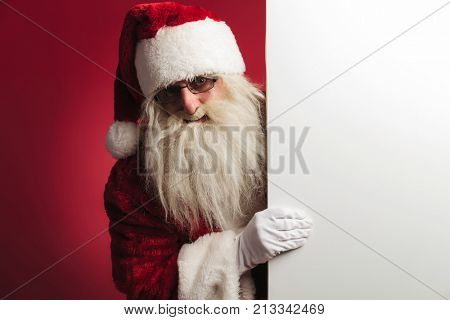 santa claus showing a big blank board on red background