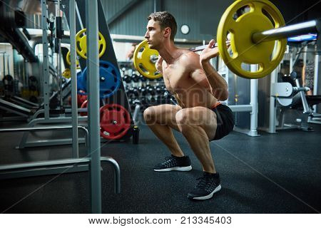 Side view portrait of handsome muscular man with bare chest squatting with heavy barbell during workout in modern sports club, copy space