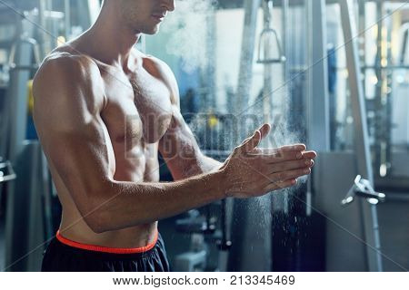 Side view of unrecognizable muscular man with bare chest rubbing hands with magnesium powder while working out in modern gym, copy space