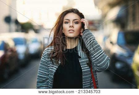 Amazing joyful pretty girl with long brunette hair. posing outdoor. Close up fashion street stile portrait