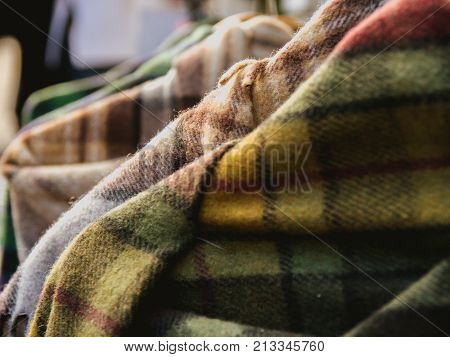 closeup of tartan shawls hung in a shop display for sale