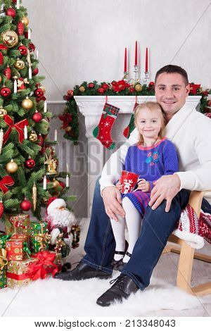Christmas or New year celebration. Happy father and daughter sitting in chair near Christmas tree with xmas gifts. A fireplace with christmas stocking on background