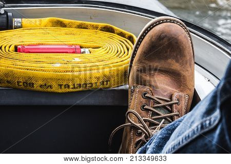 men's foot wearing tough boots and jeans on board a ship with a fire hose