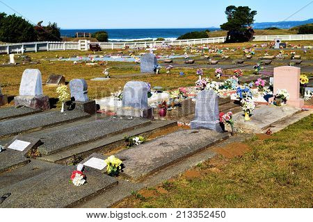 October 12, 2017 in Smith River, CA:  Old headstones on grave sites surrounded by flowers taken at the Smith River Cemetery in Smith River, CA where people can get buried and visit graves of loved ones while overlooking the Pacific Ocean