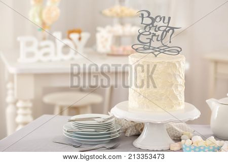 Stand with delicious cake for baby shower party on table indoors
