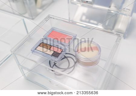 Cosmetic Makeup Items In The Drawer Of Transparent Acrylic Beauty Organizer On White Table