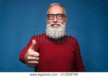 Happy modern old bearded man in warm sweeter show thumb up and happy smiling. Isolate on blue background. Successful and handsome adult bearded man of enjoying him emotions. Show ok and happy emotions