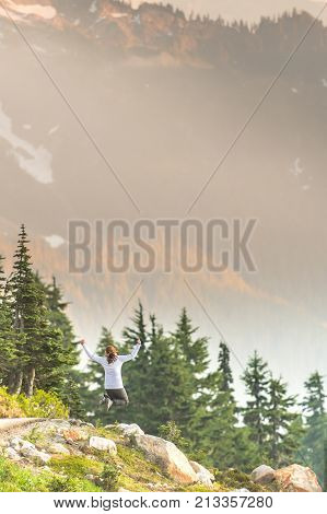 Bright Afternoon Sun Shines on Woman Leaping in cascade mountains