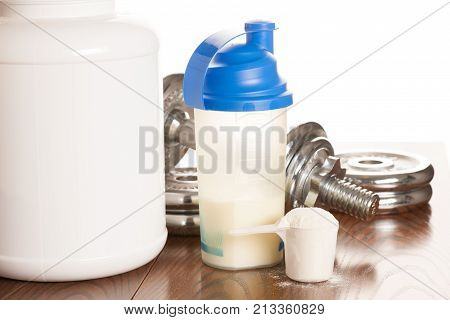 Protein Powder In Scoope With Dumbbells In Background - Whey