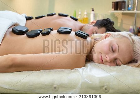Stone therapy in spa salon. Relaxed young couple receiving hot stone therapy at beauty spa. Beautiful young couple enjoying hot stone therapy in spa centre.