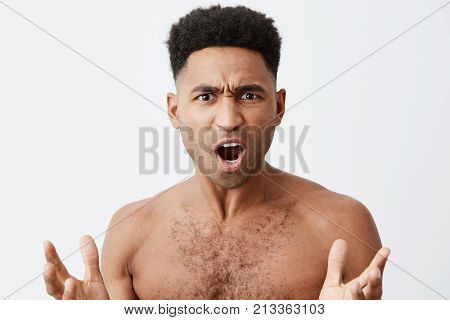 What the heck. Close up of beautiful black-skinned man with curly hair without clothes spreading hands with confused expression, when his favourite football team losing match.