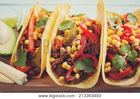 Mexican tacos with minced beef, vegetables and salsa. Tacos al pastor on wooden blue rustic background.