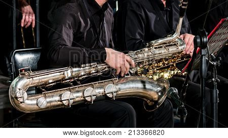 Baritone saxophone on the musician's lap. Orchestras in black clothes are sitting on chairs.