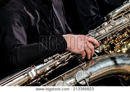 A musician in black clothes sits and holds a baritone saxophone with his right hand. Close-up For information on the musical theme.