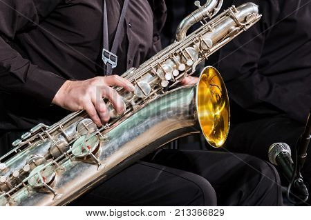 The baritone saxophone lies on the knee of the musician in a black shirt and trousers. The right hand lies on a wooden wind instrument. Close-up.