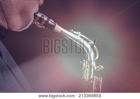 An elderly man plays a jazz melody on a saxophone. Tinted. Backlight.