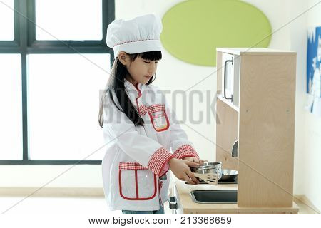 Asian girl playing as chef occupation in kindergarten class kid occupation education concept