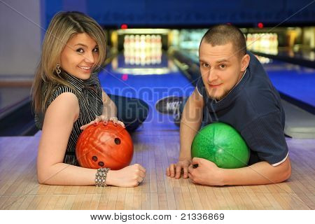 Man and woman lie on parquet leaning against an elbow and everybody holds ball for bowling, focus on hands girl