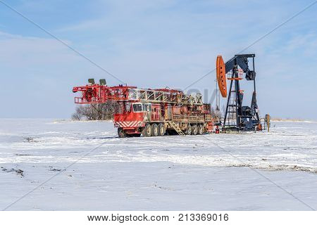 self-propelled red color drilling rig and pump jack in winter time on the field with white snow and blue sky