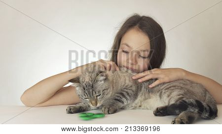 Beautiful cheerful teen girl with a cat playing with green fidget spinner on a white background