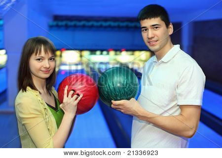 Girl and youth turned  to each other and adjoin balls for bowling