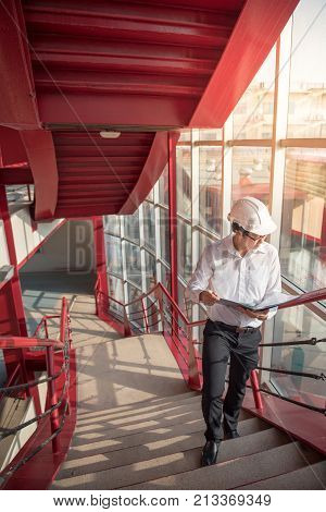 Young Asian Engineer or Architect holding files and architectural drawing wearing personal protective equipment safety helmet at construction site. Civil engineering Architecture and building concept
