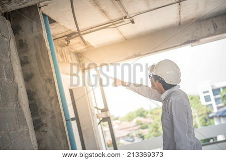 Engineer or Architect checking building while wearing a personal protective equipment safety helmet at construction site. Civil engineering Architecture and building project concepts