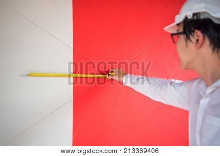 Young Asian engineer man using tape measure (measuring tape) on red and white wall at construction site Length measurement tool or equipment for building construction working