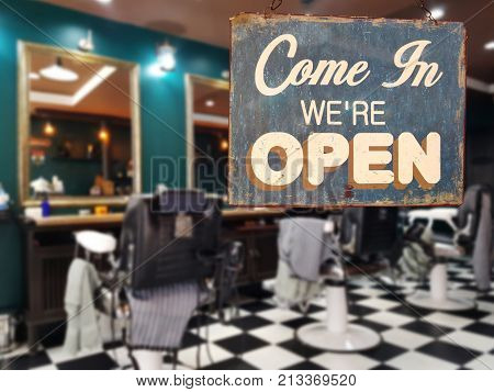 a business vintage sign that says 'Come in We're Open' on barber and hair salon shop window. image of abstract blur barber and hair salon shop business without people for background usage