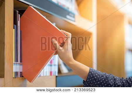 male hand choosing and picking orange book in public library education research and self learning in university life concepts
