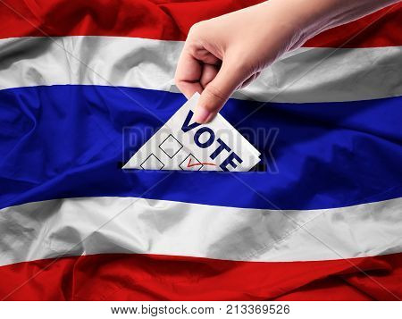 democracy and elections in Thailand concept. close up hand of a person casting a ballot at elections during voting on canvas Thailand flag background.