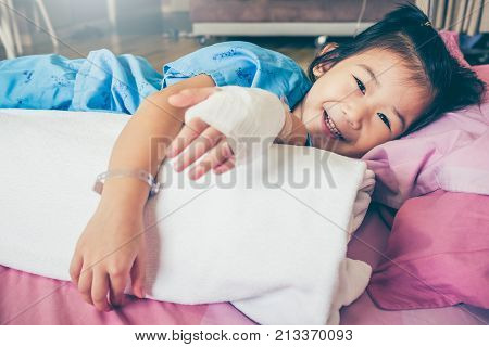 Illness asian child lying down on sickbed and looking at camera admitted in hospital and saline intravenous (IV) drip on hand. Girl smiling happily. Health care stories. Vintage film filter effect. poster