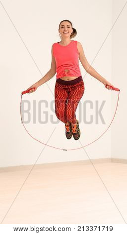 Young woman in sportswear with jumping rope indoors